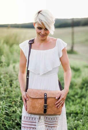A front view of woman standing in nature with a brown leather bag.