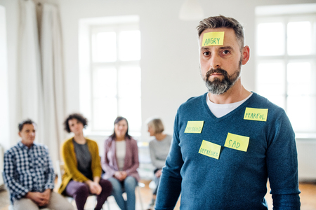 Mature man standing with negative emotions adhesive notes during group therapy.