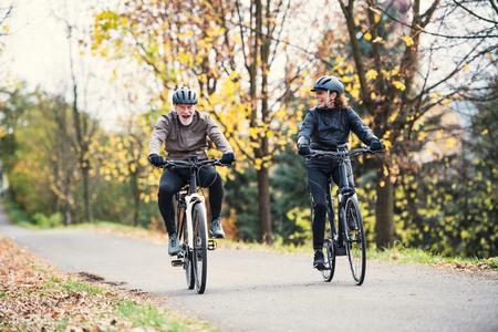 Ein älteres Paar mit Elektrofahrrädern, die im Herbst draußen auf einer Straße im Park radeln