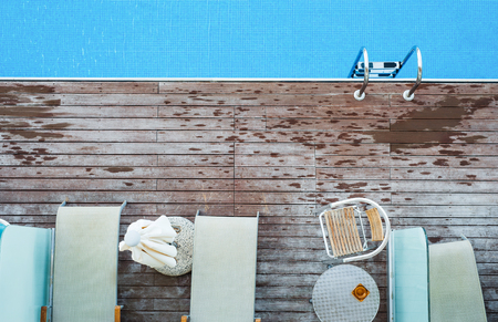 A top view of sunbathing deck and private swimming pool near beach, summer holiday concept.