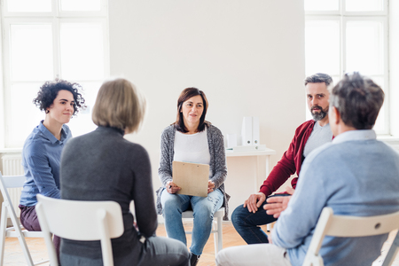 Men and women sitting in a circle during group therapy, talking. Banco de Imagens