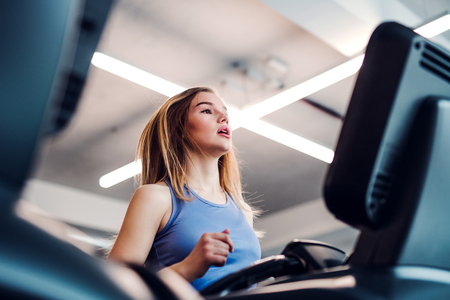 A portrait of young girl or woman doing cardio workout in a gym. Stock Photo - 117714215
