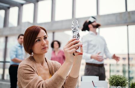 Jeune femme d'affaires ou scientifique avec une main robotique debout au bureau, travaillant. Banque d'images