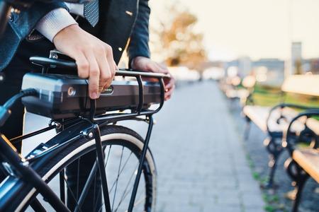 Een buik van een zakenman die een elektrische fiets in de stad opzet. Stockfoto