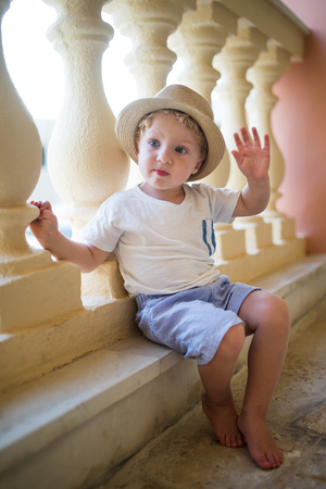 A portrait of small toddler boy sitting in front of concrete railing on summer holiday. Archivio Fotografico - 118075781