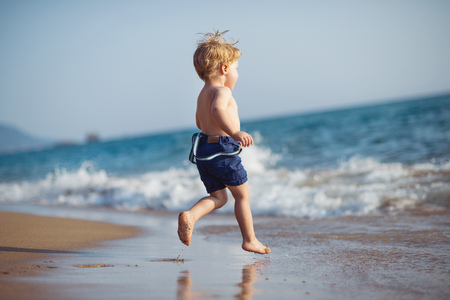 A small toddler boy with shorts running on sand beach on summer holiday. 版權商用圖片