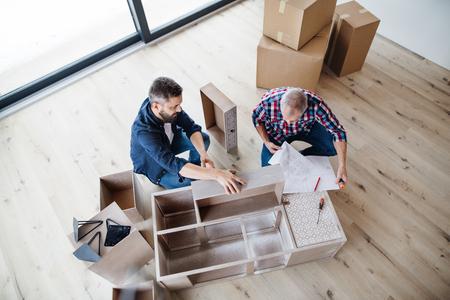 Ein Blick von oben auf den Mann mit seinem älteren Vater, der Möbel zusammenbaut, ein neues Wohnkonzept.