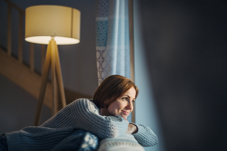 A young woman sitting indoors on a sofa at home, looking out of a window. Imagens