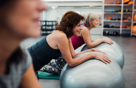 Group of cheerful female seniors in gym doing exercise on fit balls.