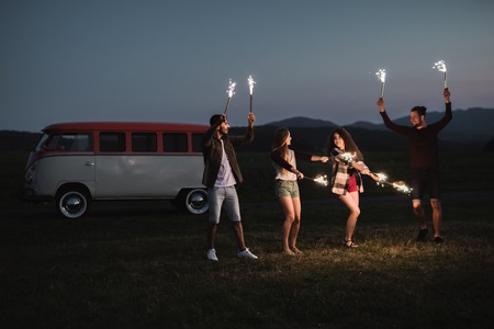 A group of friends with sparklers standing outdoors at dusk.