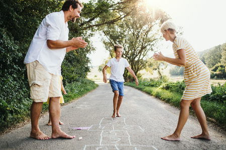A young family with small children playing hopscotch on a road in summer. Stockfoto