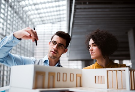 Young architects with model of a house standing in office, talking. Stock Photo