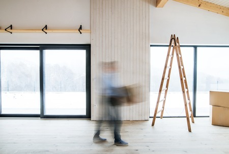 A man walking with cardboard boxes when furnishing new house. Motion blur.