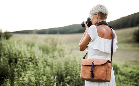 A rear view of woman with camera in nature, taking photographs. Copy space. Banco de Imagens - 118802768