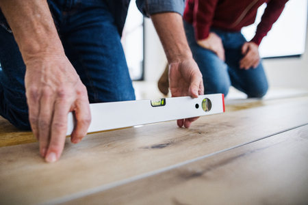 A midsection of man with his father laying vinyl flooring, a new home concept. Stock Photo