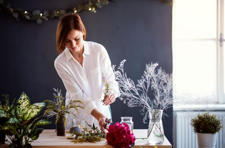 Young creative woman in a flower shop. A startup of florist business. 版權商用圖片