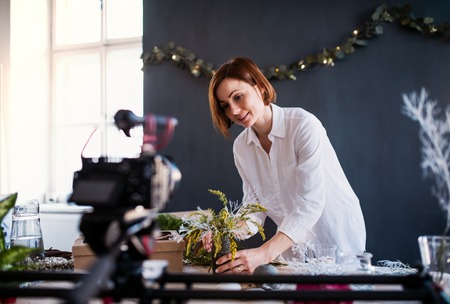 Young creative woman vlogger in a flower shop. A startup of florist business.