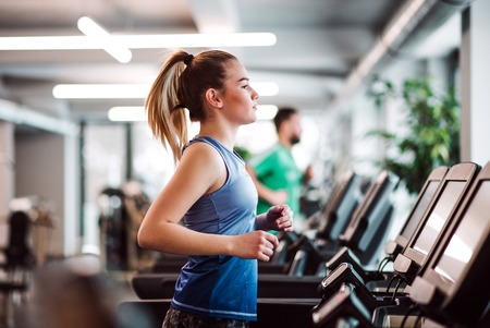 A portrait of young girl or woman doing cardio workout in a gym. Stock Photo