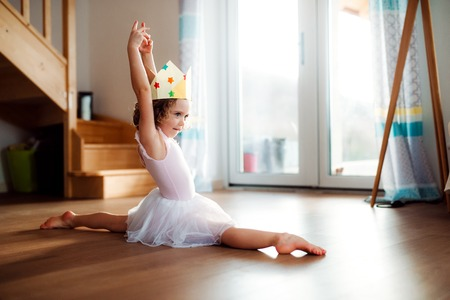 A small girl with a princess crown at home, doing gymnastic split. Stock Photo