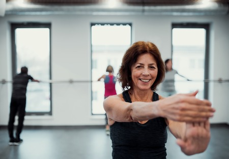 A senior woman in gym doing exercise. Copy space.