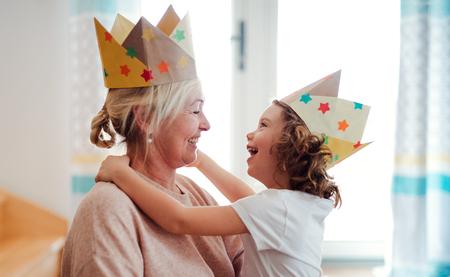 Un retrato de niña con abuela divirtiéndose en casa.