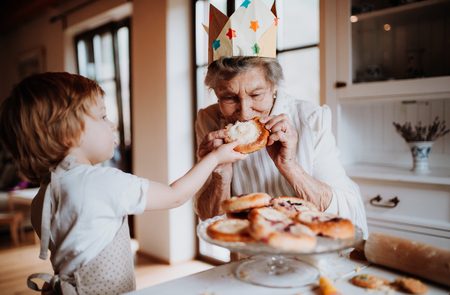 Senior grandmother with small toddler boy making and eating cakes at home.