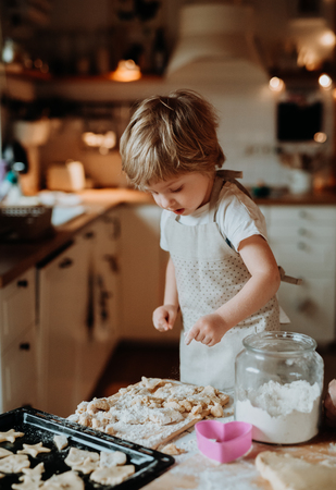 A happy small toddler boy making cakes at home. Stock Photo
