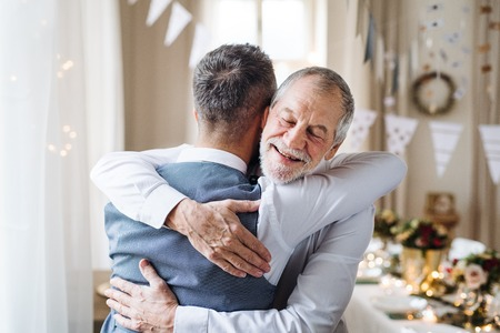 A senior and mature man standing indoors in a room set for a party, hugging.