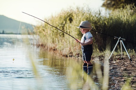A small toddler boy standing by a lake at sunset, fishing. Copy space.
