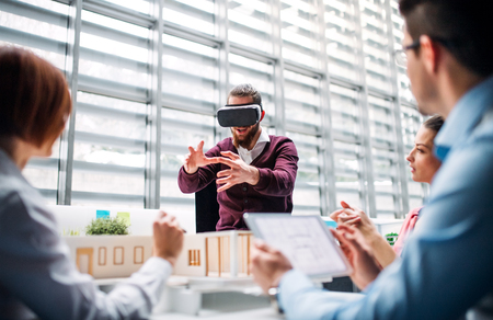 Group of young architects with model of a house and VR goggles working in office. Banque d'images - 119407584