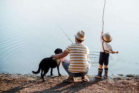 Eine Rückansicht des Vaters mit einem kleinen Kleinkindsohn und Hund im Freien, die an einem See angeln.