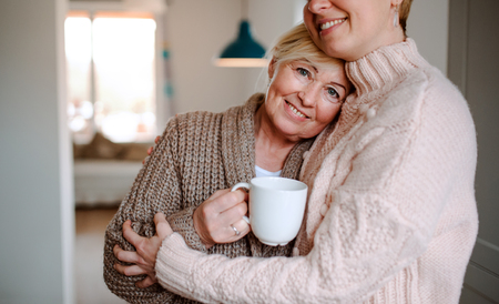 A senior woman with unrecognizable daughter at home, hugging. Stockfoto