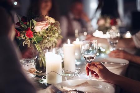 Une partie médiane d'une famille assise à une table lors d'une fête d'anniversaire à l'intérieur, tenant des lunettes. Banque d'images