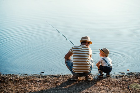 A rear view of mature father with a small toddler son outdoors fishing by a lake.