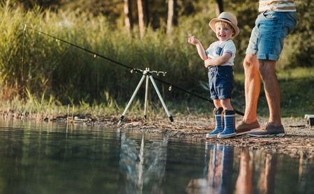 A father with a small toddler son outdoors fishing by a lake. Stock Photo