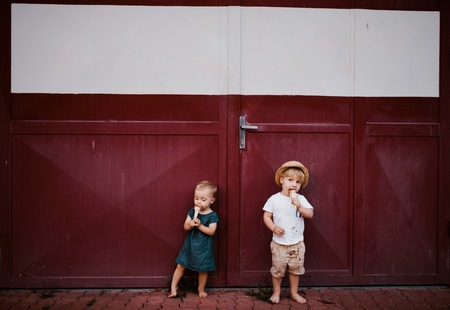 Small two toddler children outdoors in summer, eating ice cream.