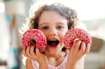 A small girl with doughnuts at home, looking at camera.
