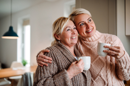A senior woman and adult daughter with coffee at home, looking out of window.