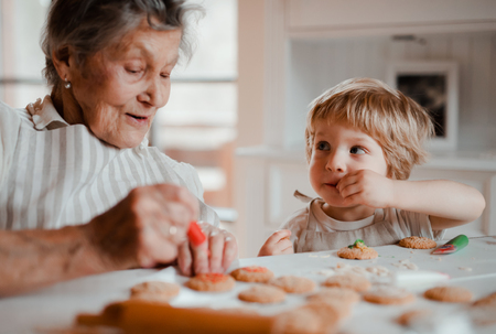 A senior grandmother with small toddler boy making cakes at home.