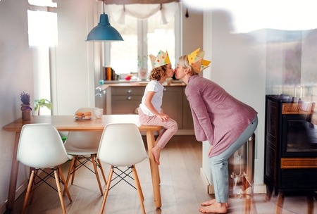 A portrait of small girl and mother with paper crown at home, kissing. Foto de archivo