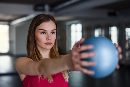 A portrait of young girl or woman doing exercise with a ball in a gym. 免版税图像