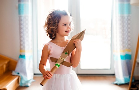 A small girl with a princess dress at home, holding a toy sword. 写真素材