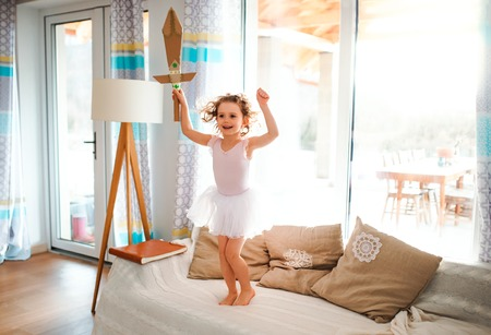 A small girl with a princess dress at home, holding a toy sword and jumping. 写真素材