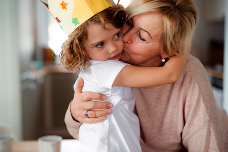 A portrait of small girl with grandmother hugging and kissing at home.