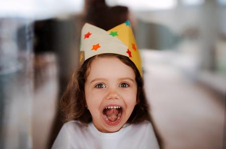 Ein kleines Mädchen mit einer Papierkrone zu Hause, Blick in die Kamera.