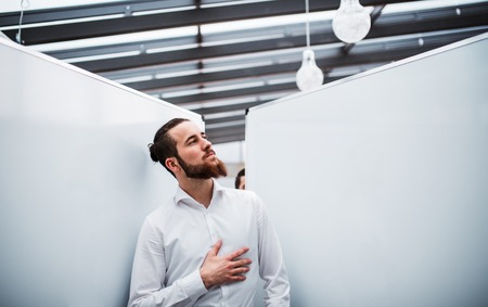 A young businessman with white shirt standing in office. Stock fotó