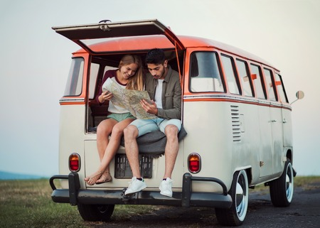 A young couple on a roadtrip through countryside, looking at a map. Reklamní fotografie