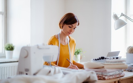 Young creative woman in a studio, startup of small tailoring business. Stock Photo