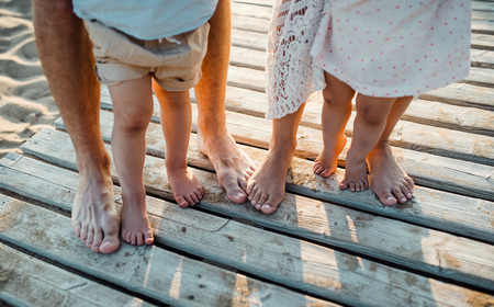 Legs and feet of family standing on beach on summer holiday, a midsection. Banco de Imagens