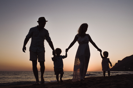 A family with two toddler children walking on beach on summer holiday at dusk.